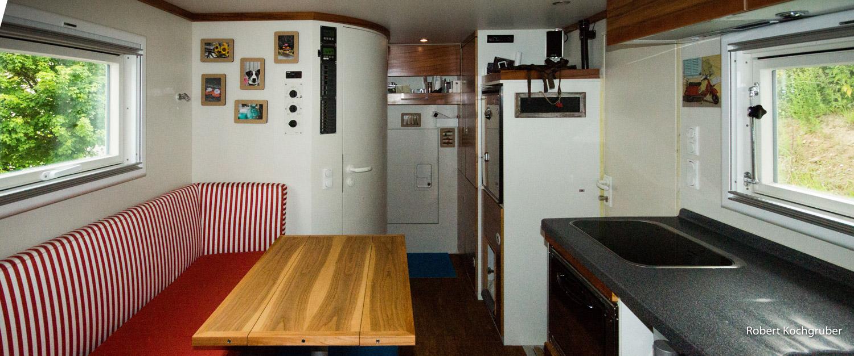 sind-reisen-in-einem-LKW-nachhaltig-expeditionsmobil-koffer-wohnraum-mit-tisch-und-küche